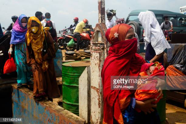 Migrant garment workers disembark from a ferry after their arrival at Mawa ferry ghat. The government of Bangladesh has eased the restrictions over...