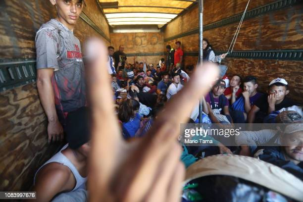 A migrant gestures as Honduran migrants from the new 'migrant caravan' wait to depart in the back of a truck to drive them toward the GuatemalaMexico...