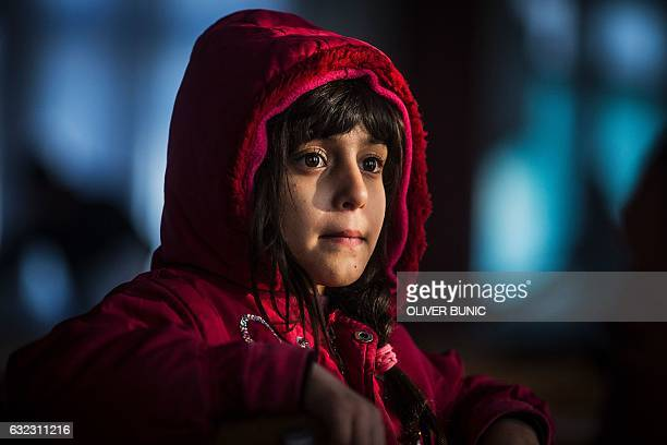 A migrant girl from Afghanistan looks on in a barrack in a refugee camp near Belgrade on January 21 2017 According to the latest figures around 7000...