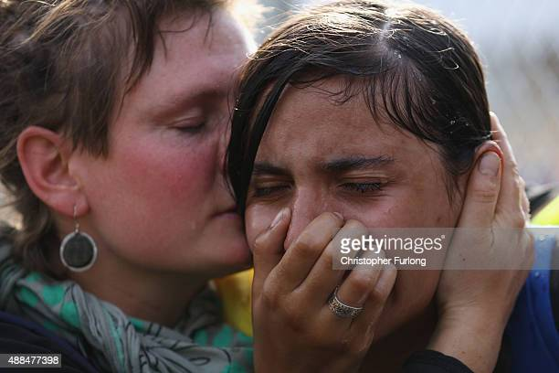 A migrant girl is comforted after being overcome by pepper spray and tear gas after Hungarian police repelled an attempt by migrants to break the...