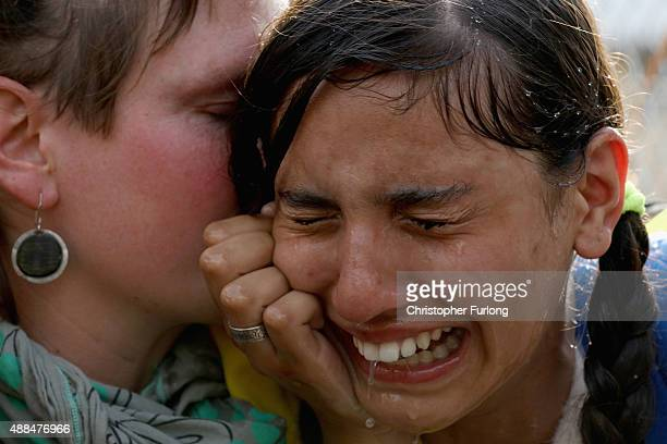 A migrant girl is overcome by pepper spray and tear gas after Hungarian police repelled an attempt by migrants to break the border post gate and pull...