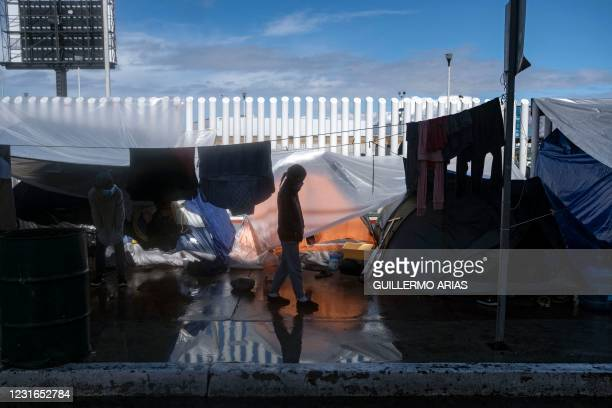 Migrant girl walks at an improvised camp outside El Chaparral crossing port as her and other wait for US authorities to allow them to start their...