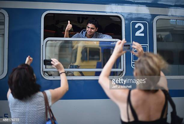 A migrant has his picture taken as a train leaves for the Austrian border from Keleti railway station on September 14 2015 in Budapest Hungary...