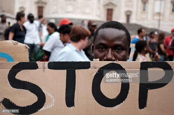 A migrant holds a placard reading stop during a demonstration in Rome on June 16 2015 Italy warned today that EU solidarity is at stake if the...