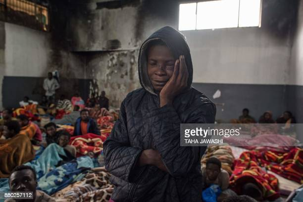 TOPSHOT A migrant holds his head as he stands in a packed room at the Tariq AlMatar detention centre on the outskirts of the Libyan capital Tripoli...