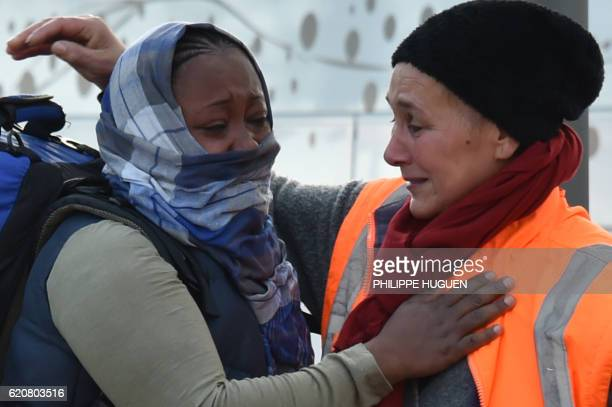 A migrant hugs with a volunteer of the association La Vie Active as she leaves the Jules Ferry reception centre next to the recently demolished...