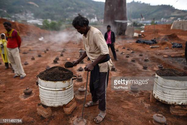 Migrant Indian labourer add sawdust and coal in firing zone of fuel storage bin chamber on Labour Day during complete nation lockdown as concerns...