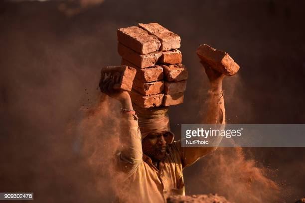 A Migrant Indian labourer stacks bricks by balancing them onto his head at a brick factory in Lalitpur Nepal on Tuesday January 23 2018 Indian...