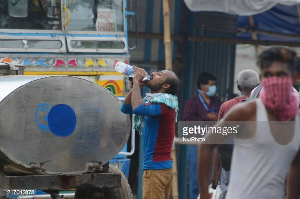 Migrant labourer drinks water during the waiting for a bus to go their native place return from Tamil Nadu by train in Barasat, District of North 24...