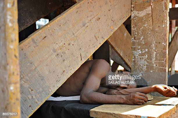 Migrant labourer takes a nap underneath a shelter in Mumbai on March 24, 2009. Inflation in India has dropped close to zero, as Asia's third-largest...