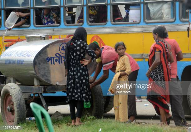 Migrant labourers collects drinking water during the waiting for a bus to go their native place return from Tamil Nadu by train in Barasat, District...