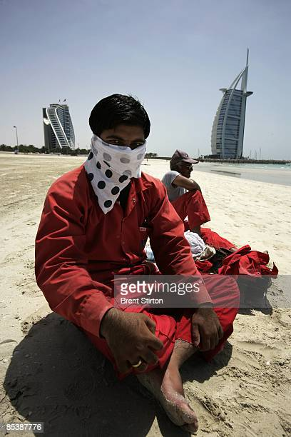 Migrant labourers take a break on a beach adjacent to the Burj Al Arab, the world's only seven star hotel, on May 1, 2006 in Dubai, United Arab...
