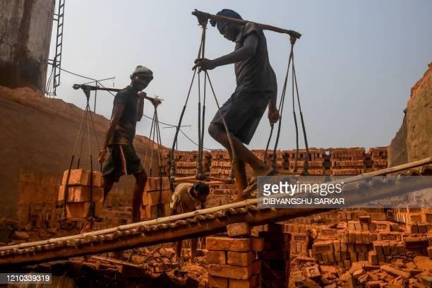 Migrant labourers work at a brick kiln factory during a government-imposed nationwide lockdown as a preventive measure against the COVID-19...