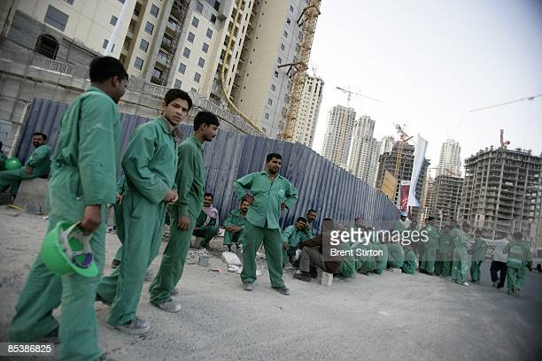 Migrant labourers working in the construction industry wait for their buses at the end of the working day in the Dubai Marina area on May 1 2006 in...