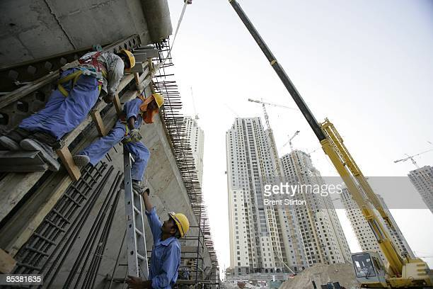 Migrant labourers working in the construction industry work on the construction of a bridge in the Dubai Marina area on May 1 2006 in Dubai United...