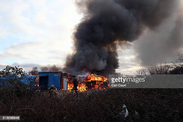 A migrant looks on as a hut burns as police officers clear part of the 'jungle' migrant camp on February 29 2016 in Calais France The French...