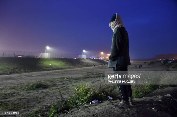 TOPSHOT A migrant looks on at the Jungle migrant camp in Calais northern France early on October 24 as an evacuation operation is planned to clear...