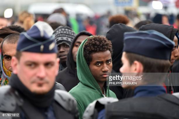TOPSHOT A migrant looks on French riot police officers hold back migrants who wait with their luggage to leave the Jungle migrant camp in Calais on...