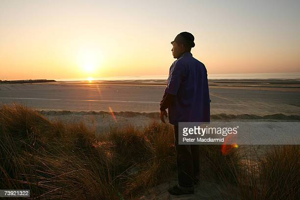 A migrant looks out to the English Channel on April 18 2007 from Calais France Many who have no money or passports spend months trying to stow away...