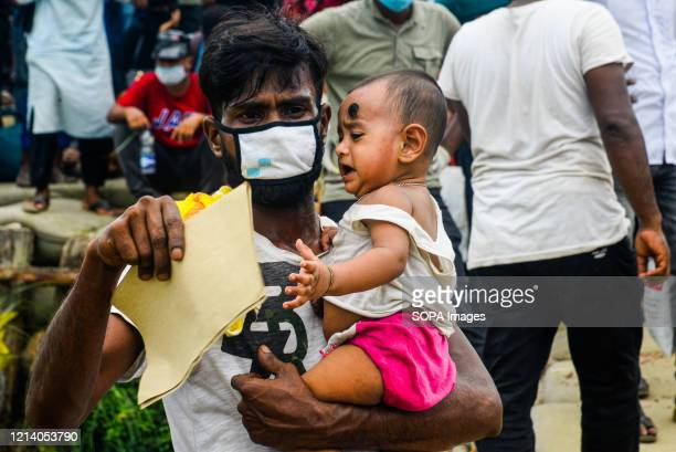 Migrant man carries a crying child as he waits for the ferry to get home for Eid ul Fitr celebrations amid Coronavirus crisis. Migrants flock at the...