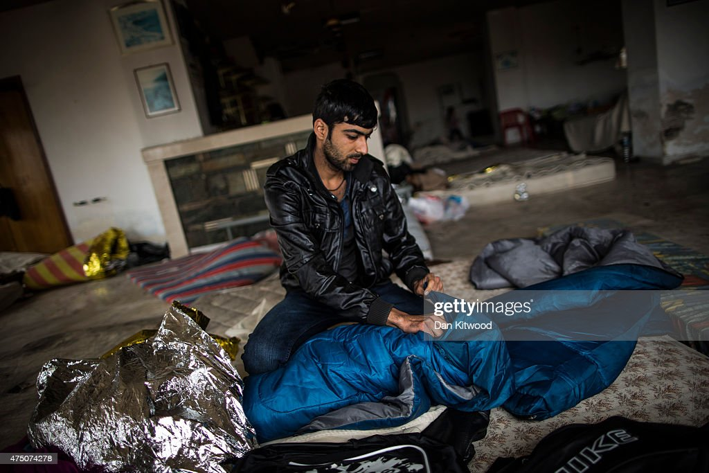 A migrant man from Bangladesh packs his belongings inside an abondoned hotel where he had been sleeping on May 29, 2015 in Kos, Greece. Migrant men women and children were queuing outside the police station to receive papers to facilitate their onward journey into Europe. Many migrants are continuing to arrive on the Greek Island of Kos from Turkey. Around 30,000 migrants have entered Greece so far in 2015, with the country calling for more help from its European Union counterparts.