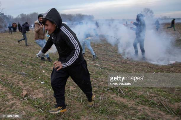 A migrant man throws a tear gas canister back at Greek border guards after clashes erupted between migrants and the Greek border guards along the...