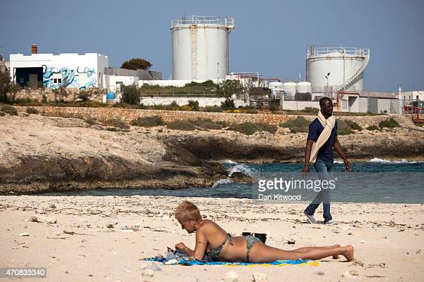 A migrant man walks across a beach on April 22 2015 in Lampedusa Italy It is expected that EU leaders in Brussels are to agree later that only 5000...