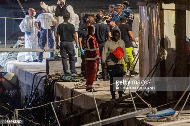 A migrant man walks near the port after being rescued by the Ocean Viking rescue ship and disembarking on Italy's southern island of Lampedusa in the...