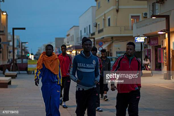 Migrant men from Nigeria walk down the main high street at dusk on April 22 2015 in Lampedusa Italy Migrants continue to arrive in Lampedusa from...