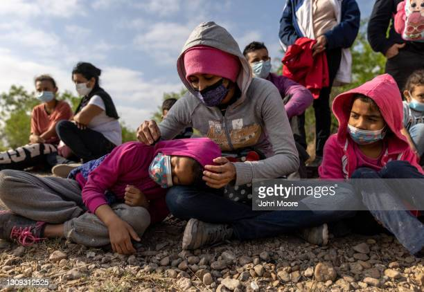 Migrant mother and daughter from Honduras sit with fellow asylum seekers after crossing the Rio Grande from Mexico into the United States on March...