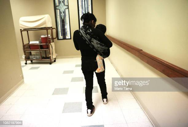 A migrant mother from Guatemala walks with her child at an Annunciation House shelter for migrants on October 12 2018 in El Paso Texas Annuciation...