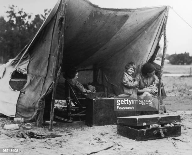A migrant mother sits in her camp while her children play photographed by Dorothea Lange in Nipomo California USA 1936