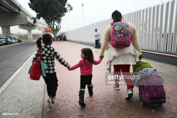 A migrant mother walks with her two daughters on their way to cross the port of entry into the US for their asylum hearing on June 21 2018 in Tijuana...
