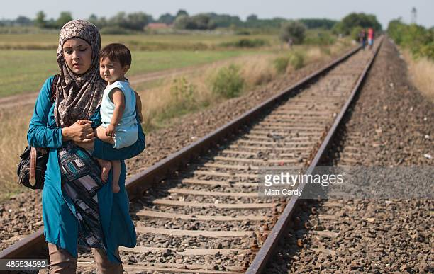 A migrant mother who has just crossed the border from Serbia into Hungary carries her child as she walks along a railway track that joins the two...