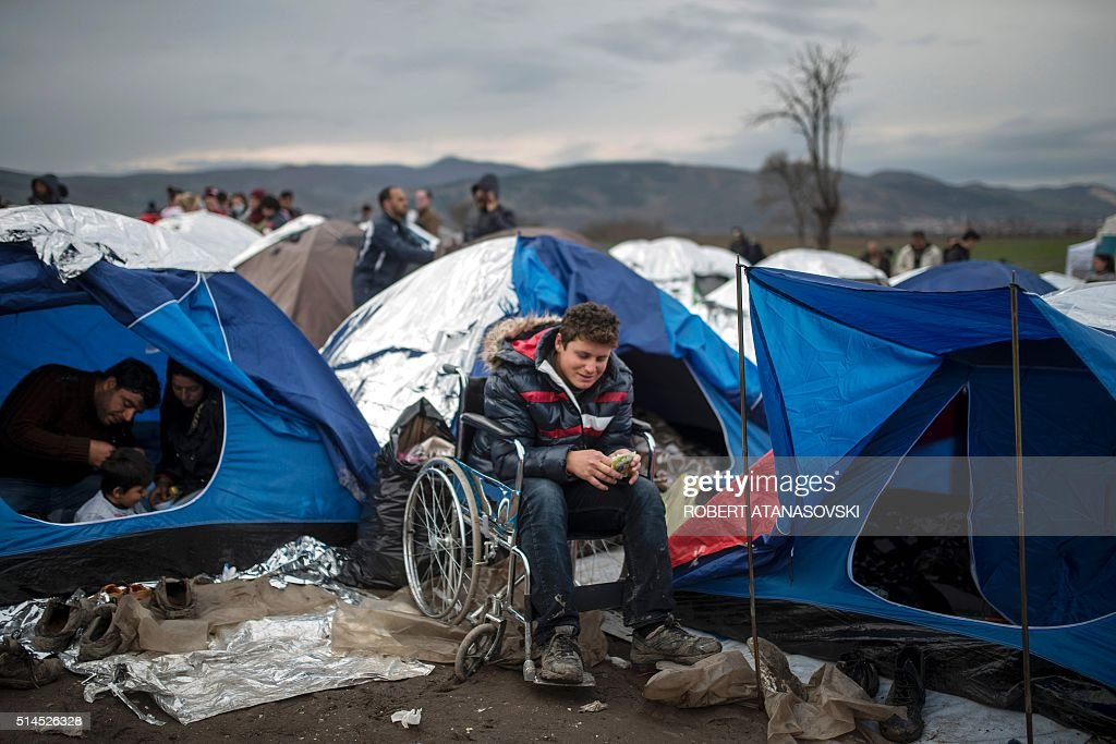 A migrant on a wheelchair waits next to tents to be allowed with other refugees and migrants to cross the border into Serbia at a makeshift c& at the ... & A migrant on a wheelchair waits next to tents to be allowed with ...