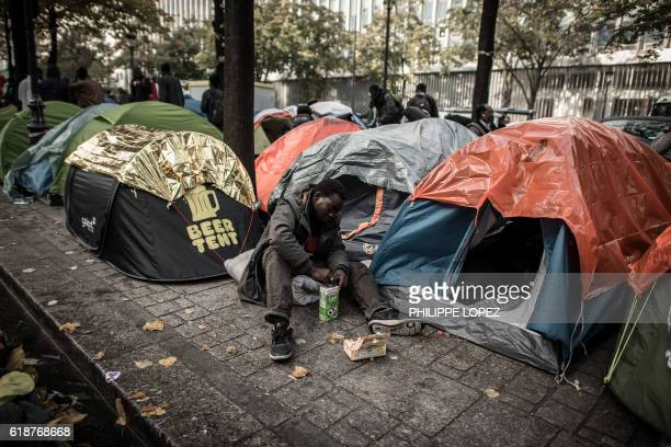 TOPSHOT A migrant opens a milk box as he sits next to tents in a street of Paris on October 28 2016 where migrants live in squalid conditions in one...