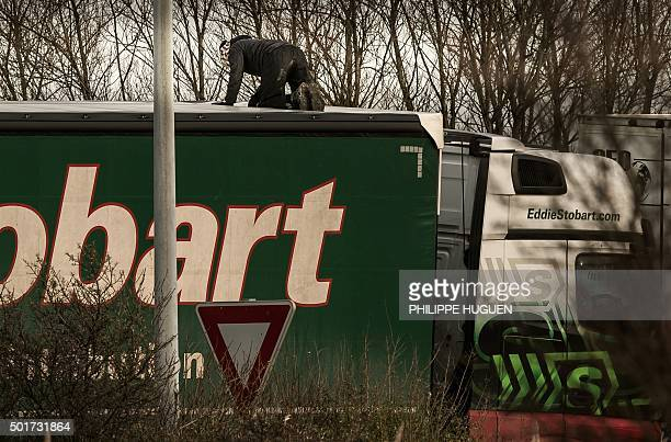 A migrant or refugee enters the trailer of a truck after having cut the tarpaulin roof on December 17 2015 on the site of the Eurotunnel in Calais A...