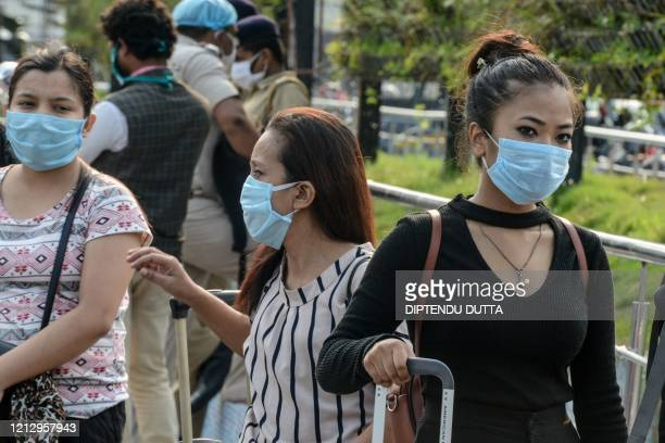 Migrant passengers from Sikkim state wait for transportation after they arrived from Chennai at New Jalpaiguri railway station following the easing...