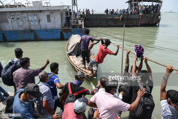 Migrant people climb on a rope as they try to get into an overcrowded ferry to travel home to celebrate Eid al-Fitr amid coronavirus crisis in...