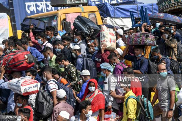 Migrant people get onto an overcrowded ferry to travel home to celebrate Eid al-Fitr amid coronavirus crisis in Munshiganj on the outskirts of Dhaka....