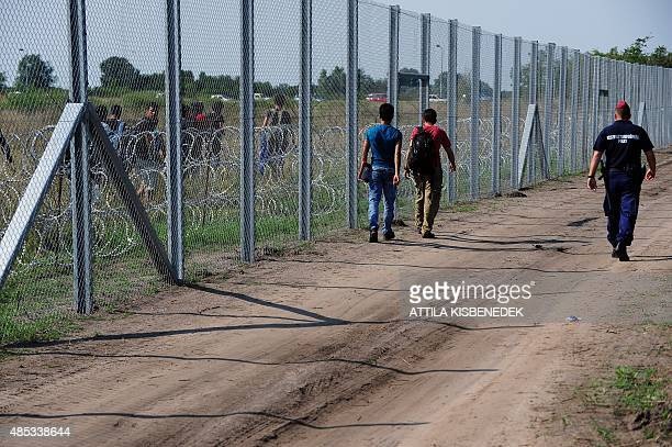 Migrant people walk on both sides of the metal fence near the Hungarian village of Asotthalom of the HungarianSerbian border on August 27 2015 As...