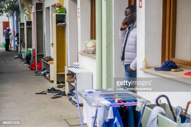 A migrant phones out of his room in the 'CAS' center at the Caracol cooperative on November 27 2017 in Venice Italy The Caracol center hosts only...