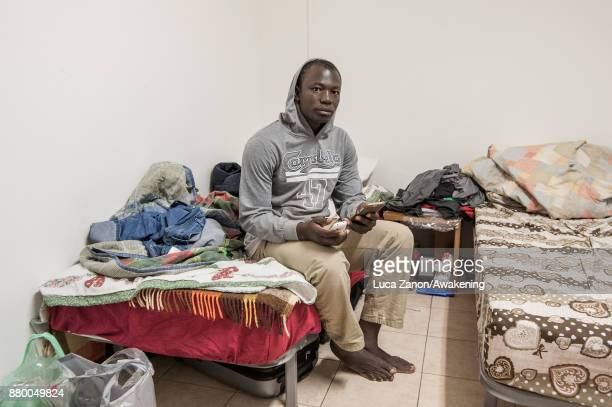 A migrant poses for a portrait in his room in the 'CAS' center at the Caracol cooperative on November 27 2017 in Venice Italy The Caracol center...