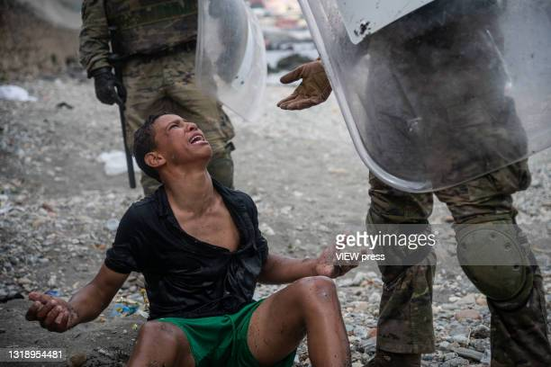 Migrant reacts as he talks to Spanish soldiers on the Tarajal beach after being intercepted when he was swimming across the border between Morocco...