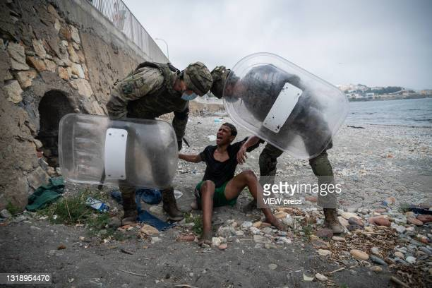 Migrant reacts while Spanish soldiers detain him on the Tarajal beach after being intercepted when he was swimming across the border between Morocco...
