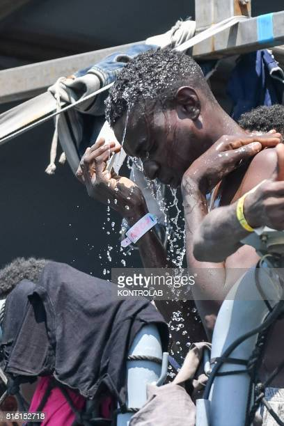 Migrant refreshes himself with water during the landing stages of migrants from the German military ship Rhein. Refugees landed are 990, among them,...