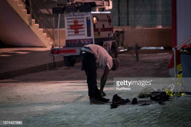 A migrant removes his shoes before entering the Care unit where the Red cross staffs will attend him Malaga Spain