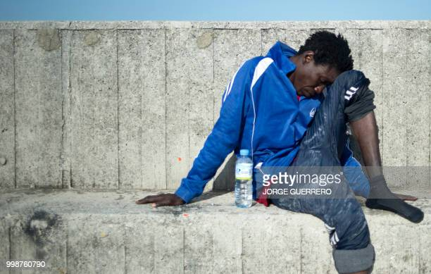 TOPSHOT A migrant rests after arriving aboard a coast guard boat at Algecira's harbour on July 14 after an inflatable boat carrying 9 migrants was...