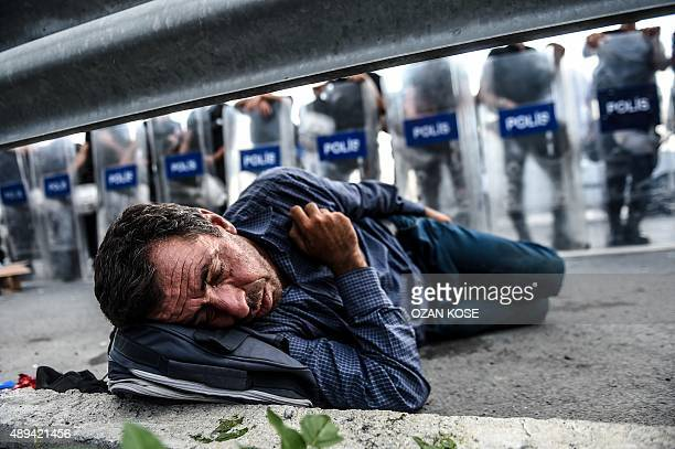 A migrant rests in front of a police barricade after Turkish riot police blocked the road towards Edirne on September 21 2015 in Istanbul A new march...