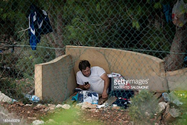 A migrant rests inside the Temporary Permanance Centre refugee camp on the italian island of Lampedusa on October 6 2013 The structure contains at...